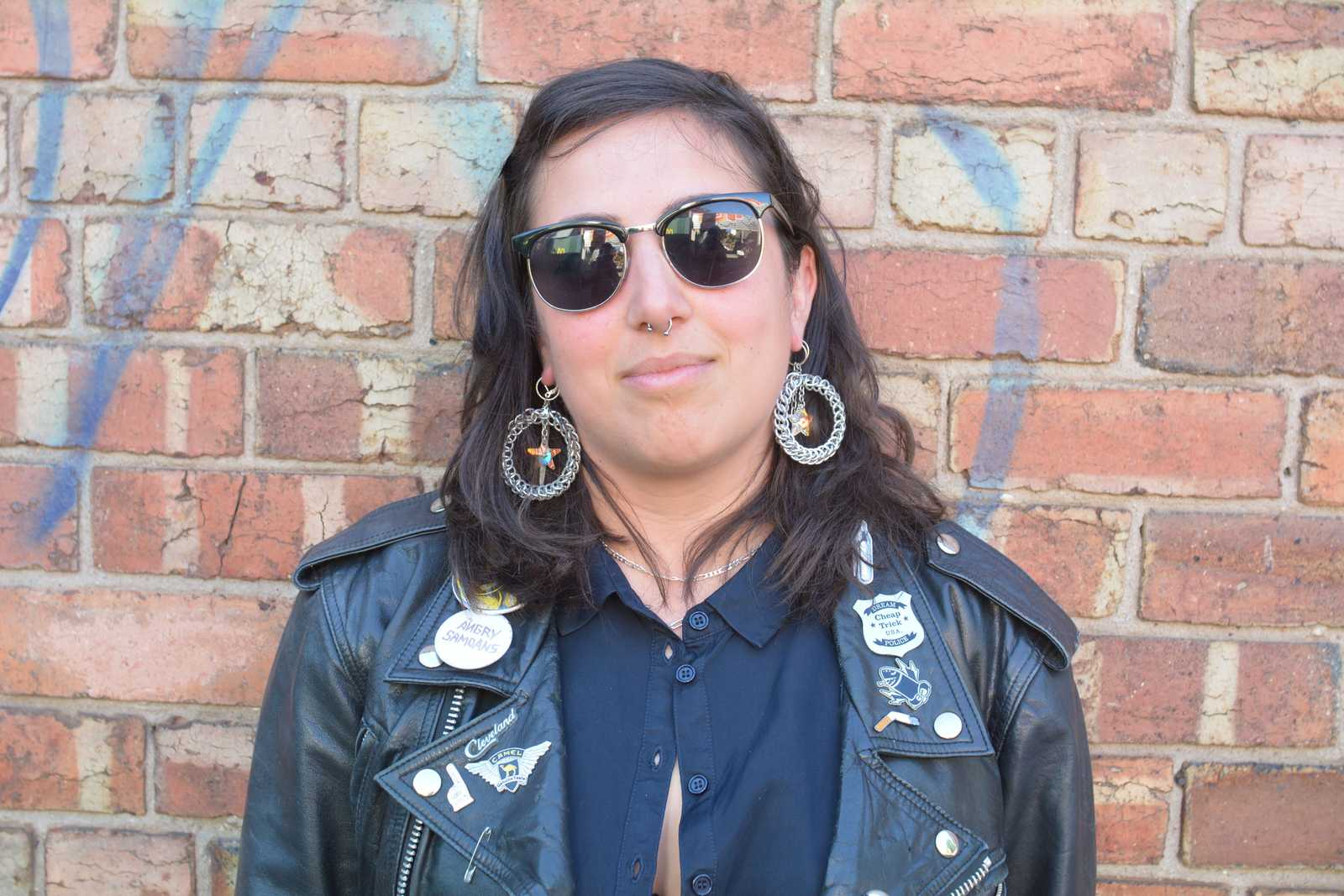 Photo of Christina wearing a black leather jacket, dark blue shirt and sunglasses, standing in front of a brick wall